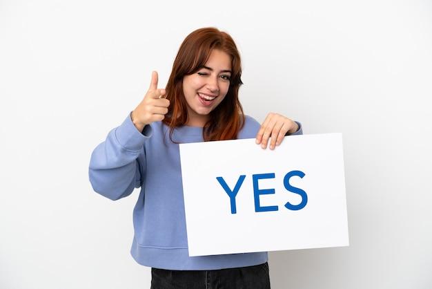흰색 배경에 격리된 젊은 빨간 머리 여성은 yes라는 문구가 적힌 플래카드를 들고 앞을 가리키고 있습니다.