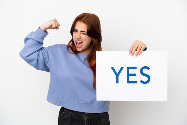 흰색 배경에 격리된 젊은 빨간 머리 여자는 강한 제스처를 하는 yes라는 문구가 적힌 플래카드를 들고 있습니다.