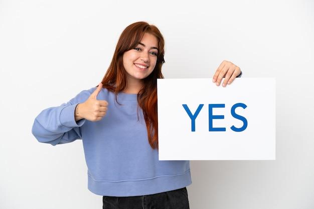 親指を上にしてテキストyesのプラカードを保持している白い背景で隔離の若い赤毛の女性
