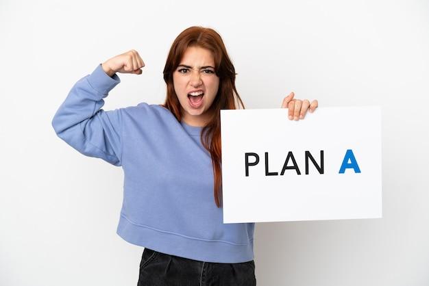 흰색 배경에 격리된 젊은 빨간 머리 여성은 plan a라는 메시지가 담긴 플래카드를 들고 강한 몸짓을 하고 있습니다.