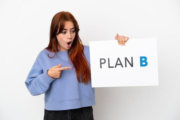 흰색 배경에 격리된 젊은 빨간 머리 여성이 놀란 표정으로 plan b라는 메시지가 적힌 플래카드를 들고 있습니다.