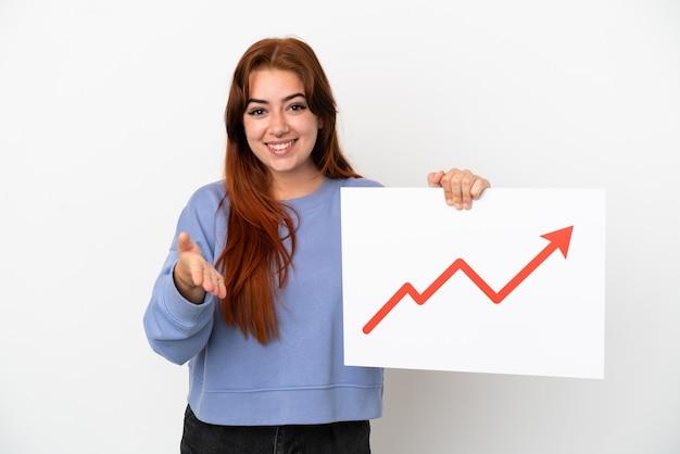 흰색 배경에 격리된 젊은 빨간 머리 여자는 거래를 하는 성장하는 통계 화살표 기호가 있는 기호를 들고 있습니다.