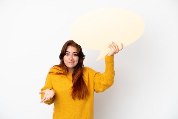 Молодая рыжая женщина изолирована на белом фоне, держа пустой речевой пузырь и сомневаясь