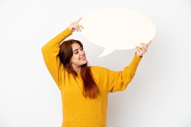 Молодая рыжая женщина изолирована на белом фоне, держа пустой речевой пузырь