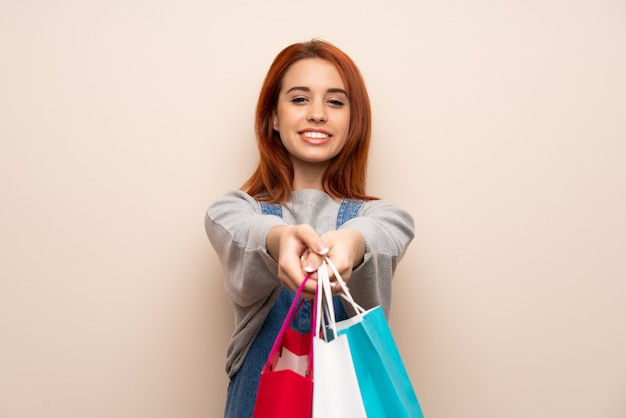 Young redhead woman over isolated wall holding a lot of shopping bags