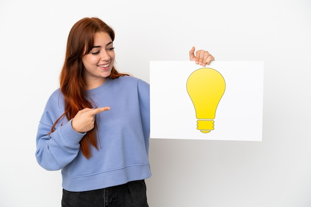 Young redhead woman isolated on white background holding a placard with bulb icon and pointing it