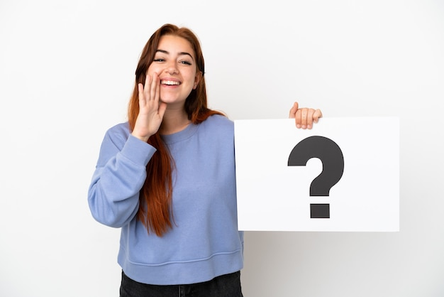 Young redhead woman isolated on white background holding a placard with question mark symbol and shouting