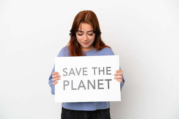 Young redhead woman isolated on white background holding a placard with text save the planet