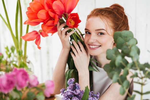 Young redhead woman looking up and holding red tulips