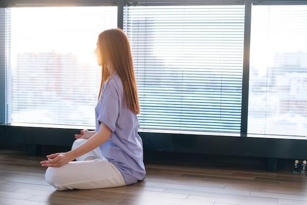 蓮華座の窓の近くの床に座って、呼吸ヨガの練習を瞑想している若い赤毛の女性。ホームオフィスで目を閉じて瞑想する白人の平和な女性。
