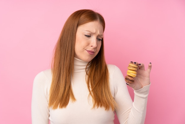 Young redhead woman over pink holding colorful french macarons with sad expression
