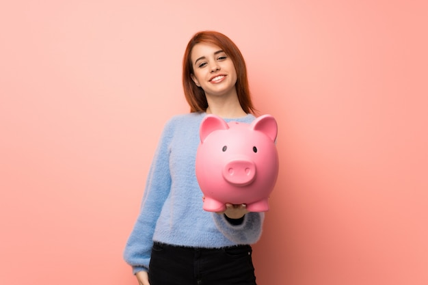 Young redhead woman over pink holding a piggybank