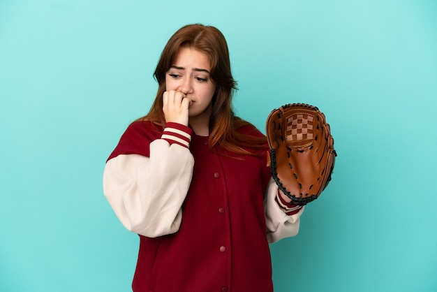 Young redhead woman playing baseball isolated on blue background having doubts