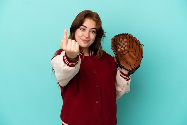 Молодая рыжая женщина играет в бейсбол на синем фоне, делая приближающийся жест