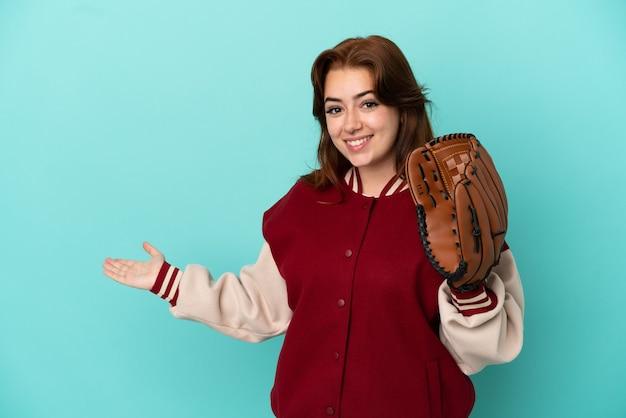 来るように誘うために手を横に伸ばして青い背景で隔離の野球をしている若い赤毛の女性