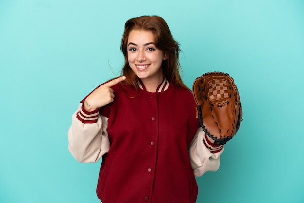 親指を立てるジェスチャーを与える青い背景で隔離の野球をしている若い赤毛の女性