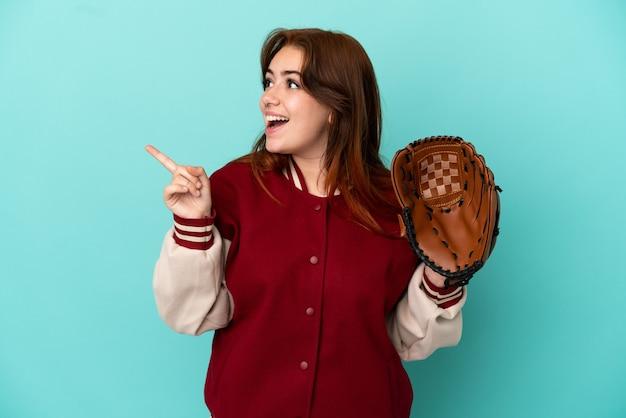 Молодая рыжая женщина играет в бейсбол на синем фоне, намереваясь реализовать решение, подняв палец вверх
