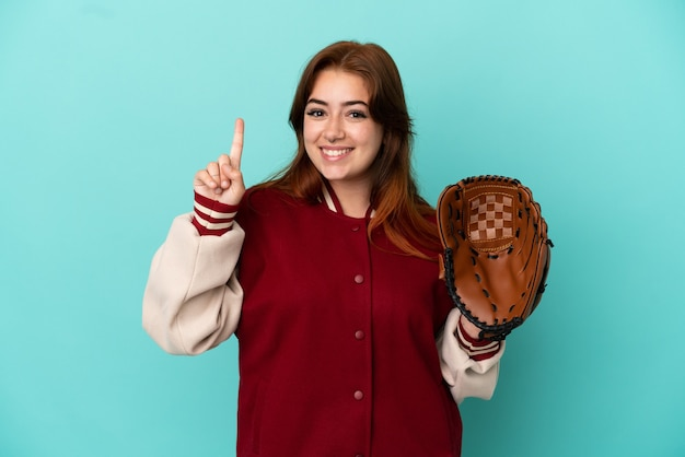 Молодая рыжая женщина играет в бейсбол на синем фоне, показывая и поднимая палец в знак лучших