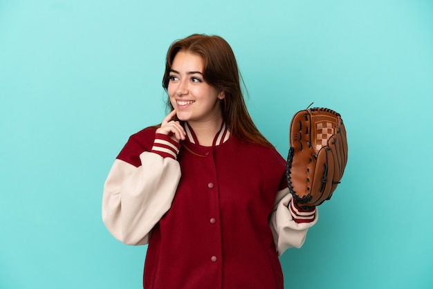 Молодая рыжая женщина играет в бейсбол на синем фоне, думая об идее, глядя вверх
