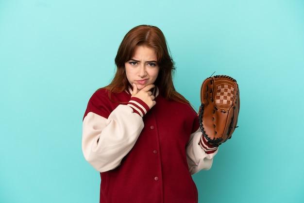 Молодая рыжая женщина играет в бейсбол на синем фоне мышления