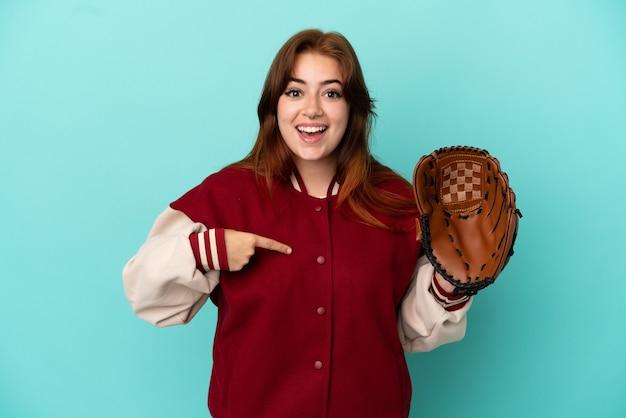 Молодая рыжая женщина играет в бейсбол на синем фоне с удивленным выражением лица