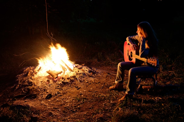 Young redhead woman playing guitar near bonfire at night camp
