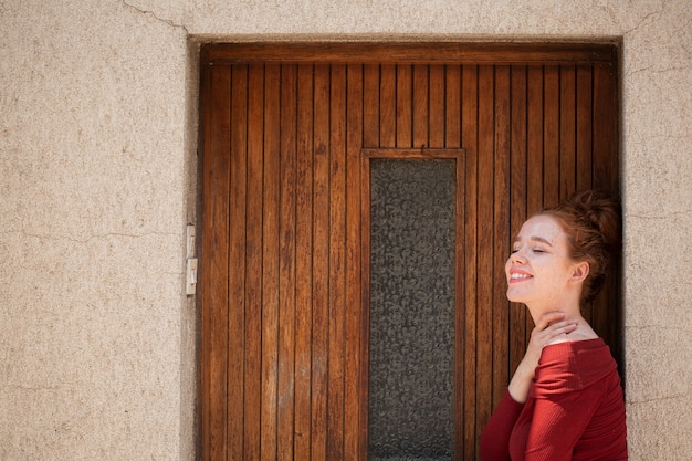 Young redhead woman posing in front of door