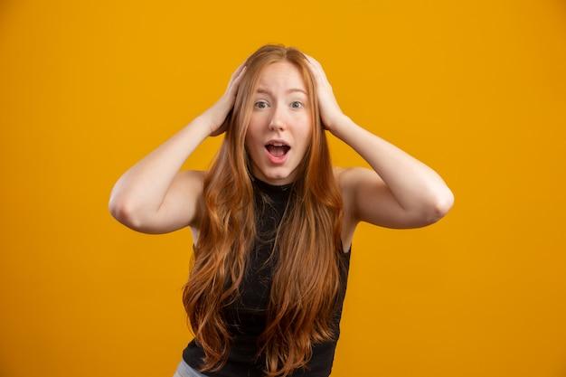머리에 손을 올리는 젊은 빨간 머리 여자, 입을 벌리고, 매우 운이 좋은 느낌, 놀라움, 흥분 및 노란색 벽에 행복.