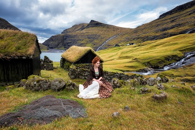 A young redhead woman sits near a stone fence in old-fashioned clothes. faroe islands, denmark