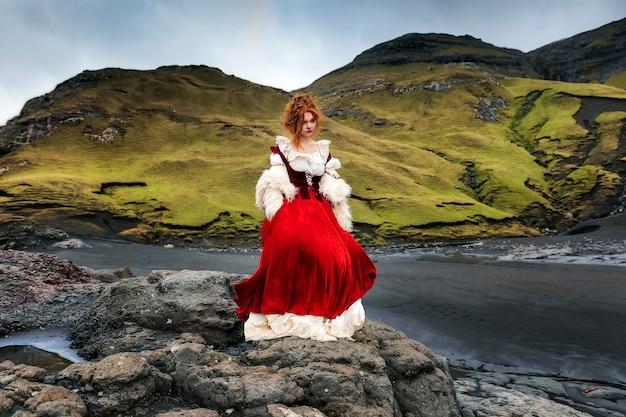 A young redhead woman stays on big stone near ocean coastline in old-fashioned clothes. faroe islands, denmark