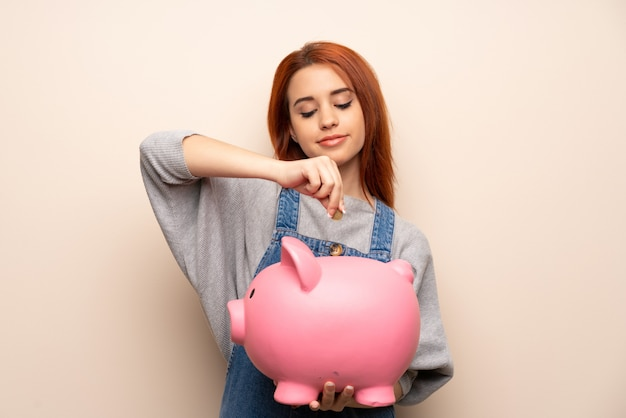 Young redhead woman   taking a piggy bank and happy because it is full