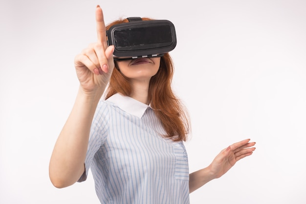 Young redhead woman using glasses of virtual reality