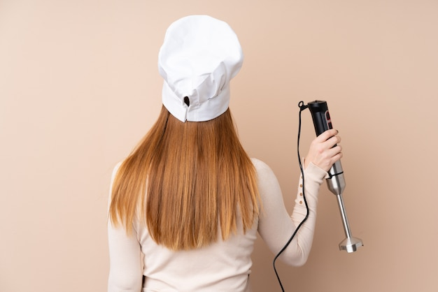 Young redhead woman using hand blender in back position