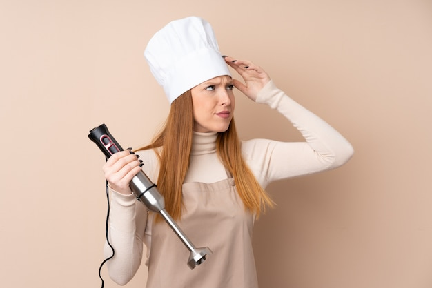 Young redhead woman using hand blender having doubts and with confuse face expression