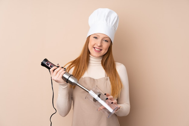 Young redhead woman using hand blender