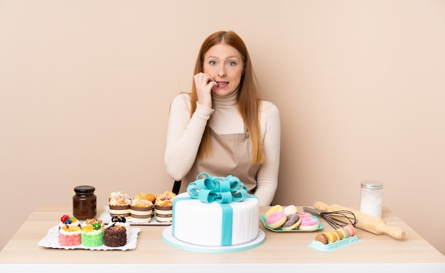 Young redhead woman with a big cake nervous and scared