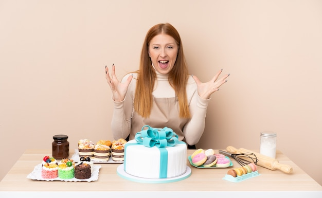Young redhead woman with a big cake unhappy and frustrated with something