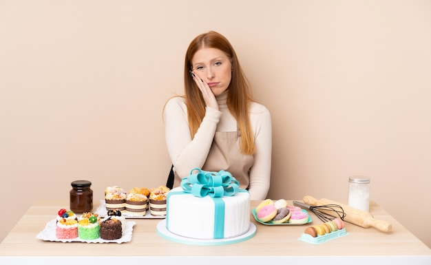 Young redhead woman with a big cake unhappy and frustrated