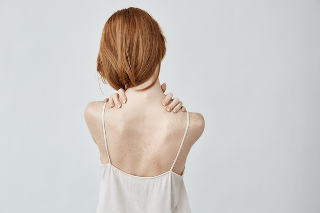 Giovane donna di redhead con le lentiggini che posano indietro