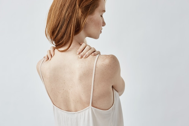Young redhead woman with freckles posing back