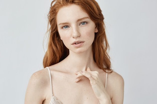 Young redhead woman with freckles.