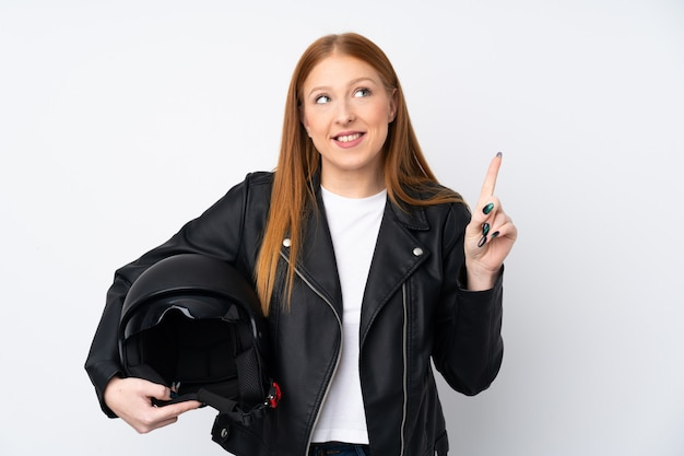 Young redhead woman with a motorcycle helmet over isolated white wall intending to realizes the solution while lifting a finger up