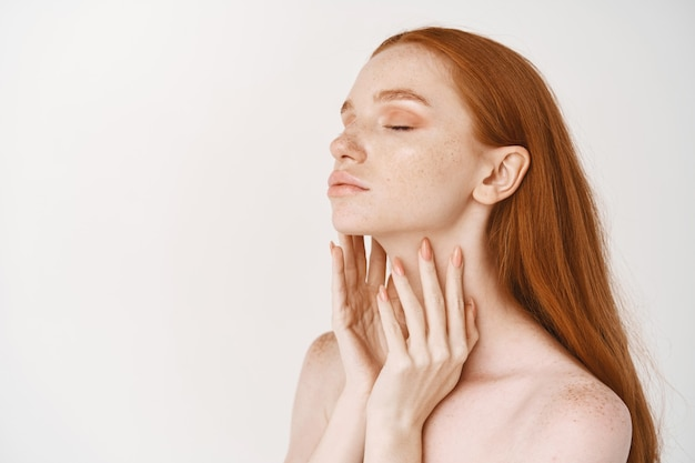 Young redhead woman with pale smooth skin, standing in profile and enjoying touching clean perfect face, concept of skincare and cosmetology