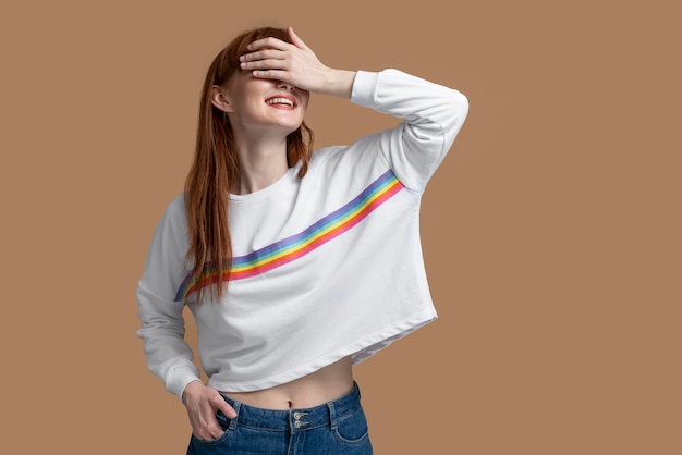 Молодая рыжая женщина с символом радуги