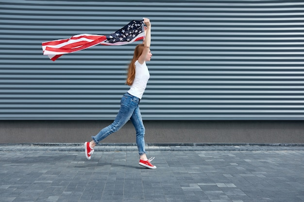 Young redhead woman with red-painted lips standing with the usa flag