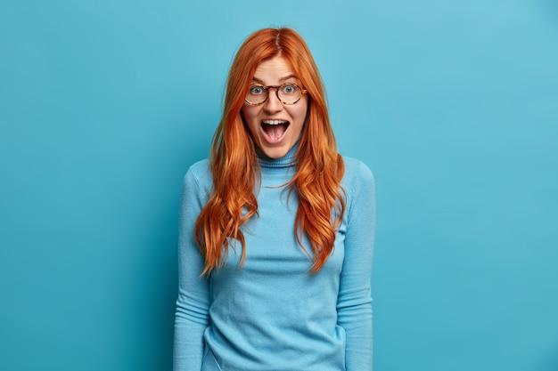 ショックを受けた表情の若い赤毛の女性は、驚異的なニュースでタートルネックを着て口を開けたまま反応します。