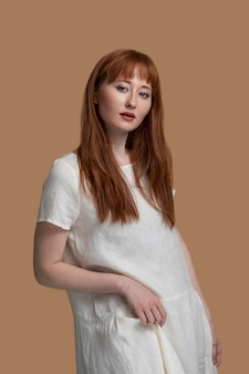 Young redhead womanin white dress