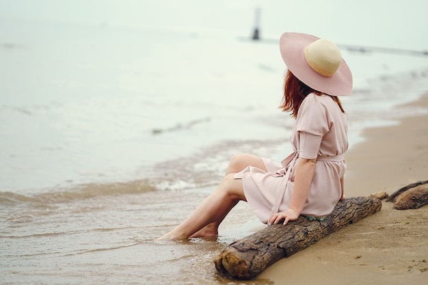 A young redheaded girl in a large round hat and pink dress sitting on the beach near ocean
