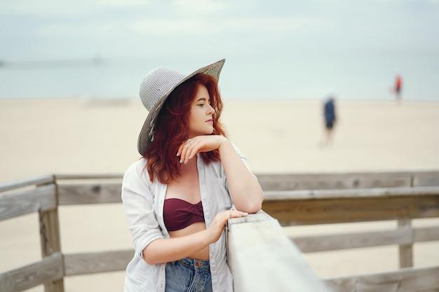 Giovane ragazza dai capelli rossi in un grande cappello rotondo e camicia bianca in piedi sulla sabbia sulla spiaggia