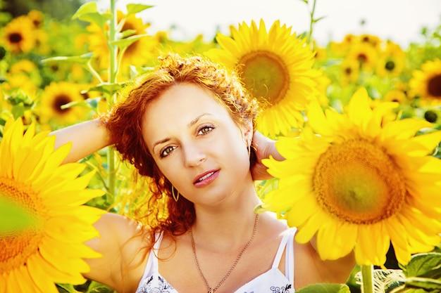 ひまわり畑の若い赤毛の女性